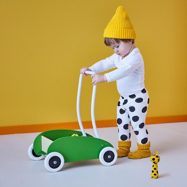 Un bambino con un cappello giallo e pantaloni bianchi a pois neri spinge un carrellino primi passi MULA verde accanto a un peluche.