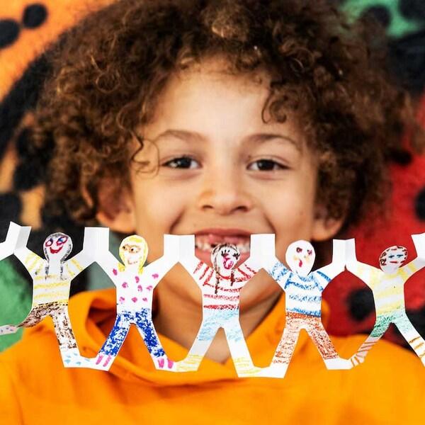 Un bambino con una felpa arancione tiene in mano una ghirlanda colorata con sagome di bambini che si tengono per mano - IKEA