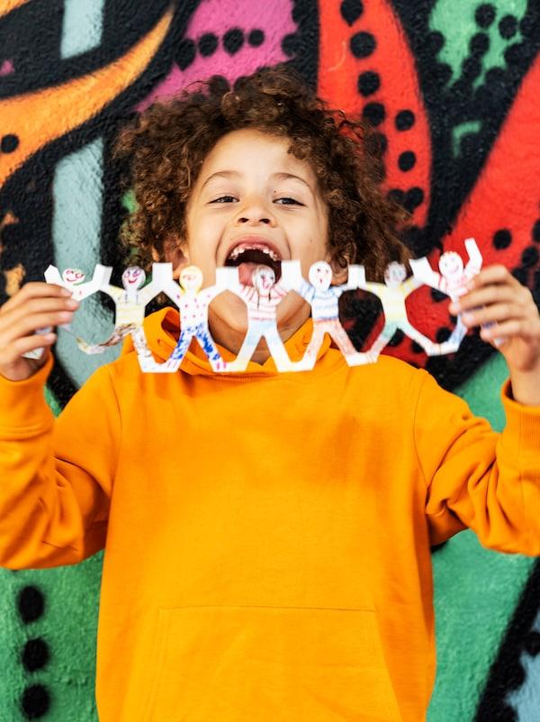 Un bambino con una felpa arancione tiene in mano una simpatica ghirlanda davanti a un muro colorato - IKEA