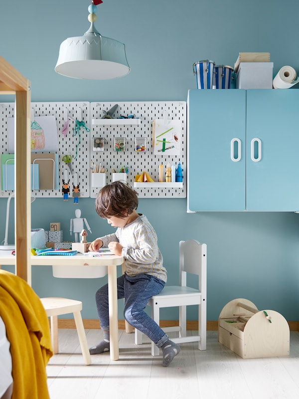 Un bambino seduto a un tavolo FLISAT su una seggiolina SUNDVIK gioca sotto una lampada a sospensione TROLLBO.