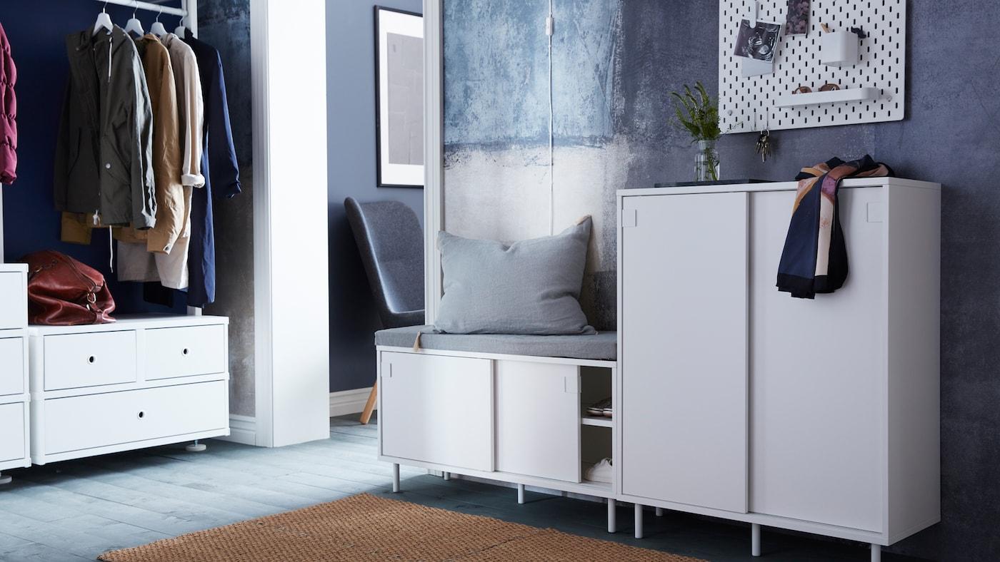 Un banc à rangement MACKAPÄR sur lequel est posé un coussin gris et une armoire MACKAPÄR où sont posés un vase et une écharpe dans un couloir.