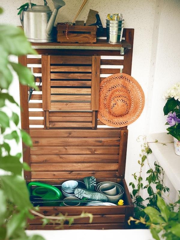 Un banc d'extérieur ÄPPLARÖ avec panneau et tablettes où l'on a disposé des outils de jardinage.