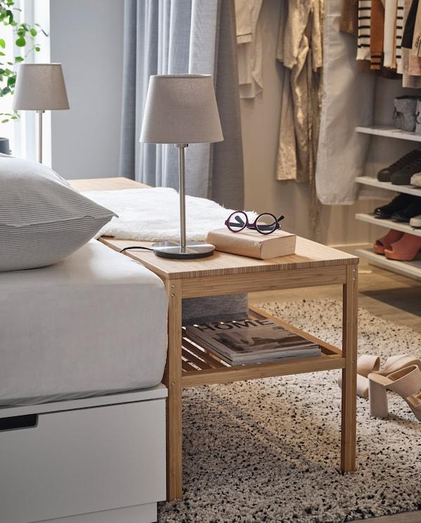 Un banc en bambou placé à côté d'un lit et servant de table de nuit. Des lampes de table, des lunettes et un livre sont posés dessus.