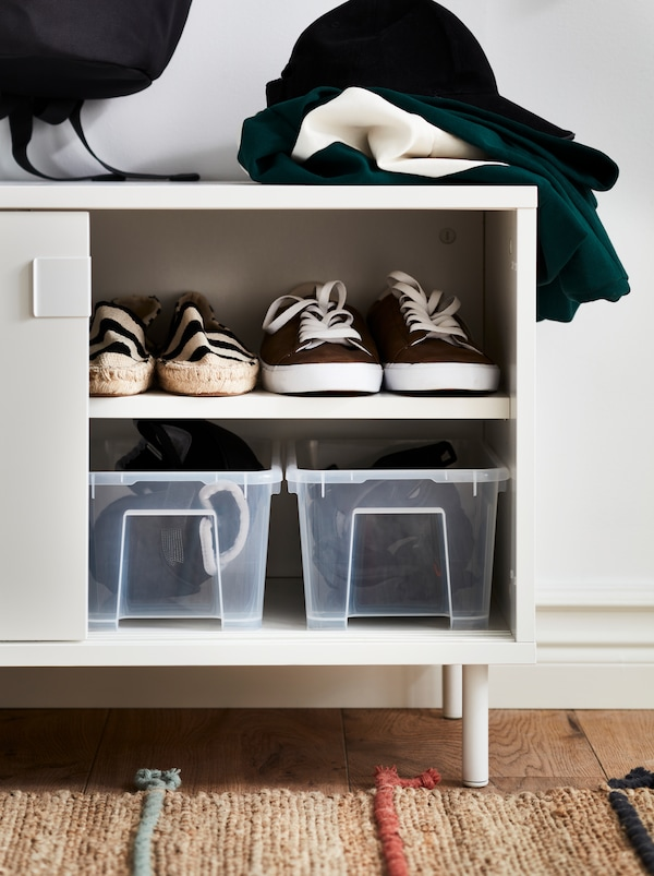 Un banc MACKAPÄR blanc à compartiments de rangement ouvert avec des boîtes transparentes et des chaussures à l'intérieur.
