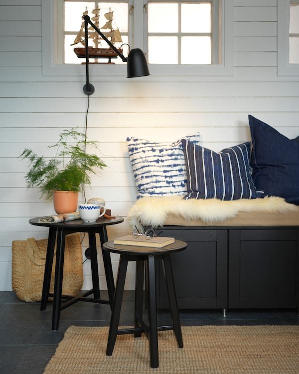 Un banco de cociña negro, coxíns azuis, un niño de mesas en negro, unha lámpada de parede negra e unha planta verde.