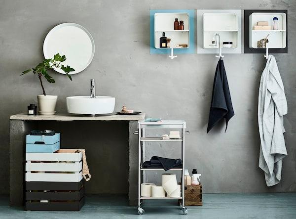 Un baño compartido organizado con distintas cajas de madera KNAGGLIG de distintos colores, un carrito GRUNDTAL y armarios de pared.