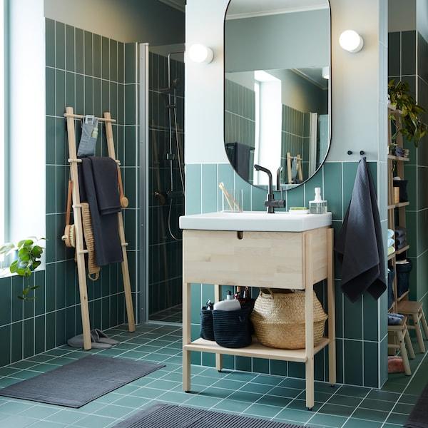 Un baño cun armario/lavabo en bidueiro/branco, un gran espello ovalado e toallas e alfombras de baño gris escuro.