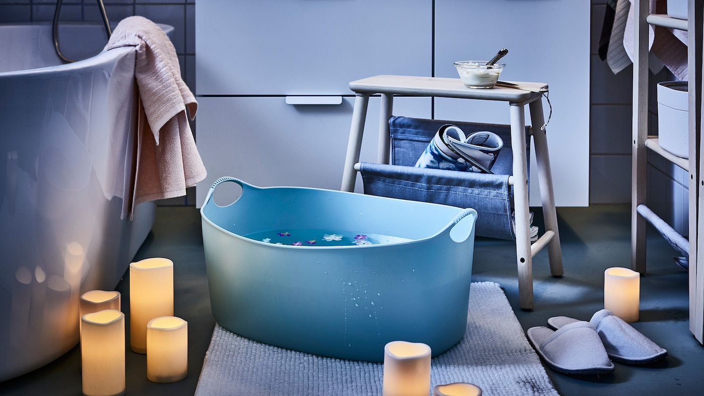 Un baño iluminado por velas de bloques LED dispersos, un taburete colocado junto a un gran baño de pies, con flores flotando en él.