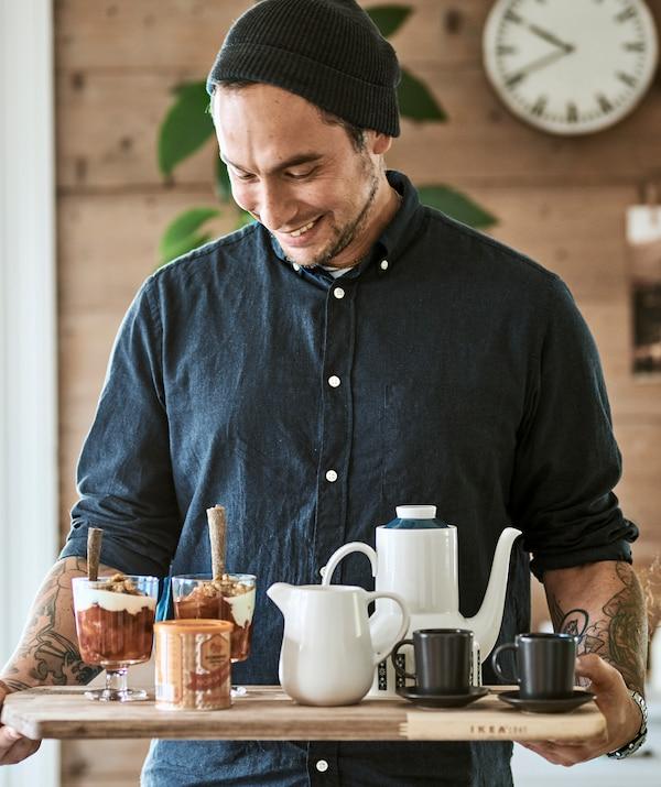 Un bărbat care poartă o căciulă pe cap folosește un tocător pe post de tavă pentru a duce un ceainic cu cafea, cești de espresso și două pahare cu granola.