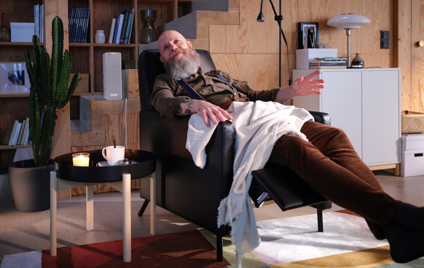 Un bărbat stă sprijinit pe spate sub o pătură într-un fotoliu rabatabil GISTAD ascultând muzică de la o boxă WiFi SYMFONISK de culoare albă.