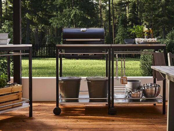 Un barbecue noir avec chariot en acier inoxydable, ustensiles de cuisine, bols, seaux avec couvercles, herbes et huiles aromatiques.