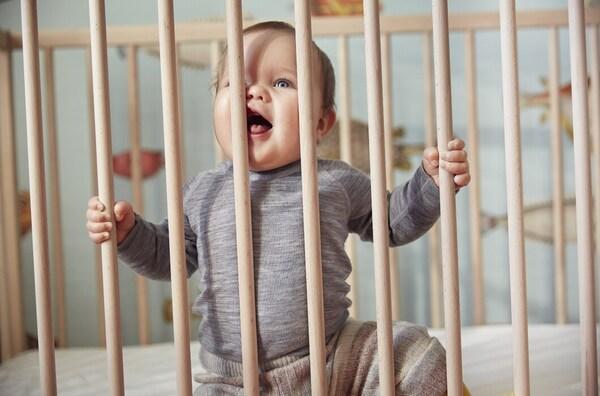 Un bébé dans un berceau assis en souriant.