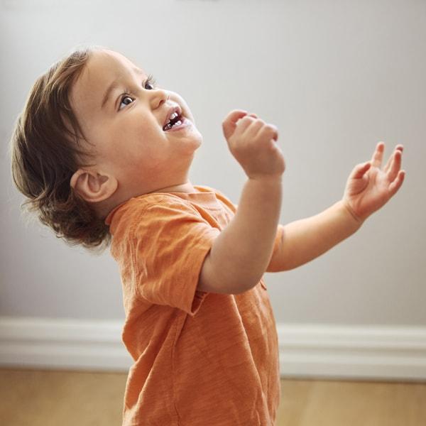 Un bébé dans une chemise orange dansant et levant les yeux.