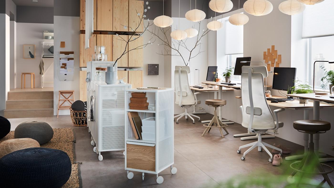 Un birou dotat cu scaune rotative JÄRVFJÄLLET ergonomice, corp de depozitare din pin IVAR și mese de lucru cu furnir din stejar.