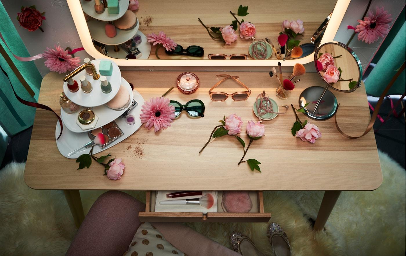 Un birou LISABO folosit drept masă de machiaj împreună cu o oglindă STORJORM cu lumini integrate.
