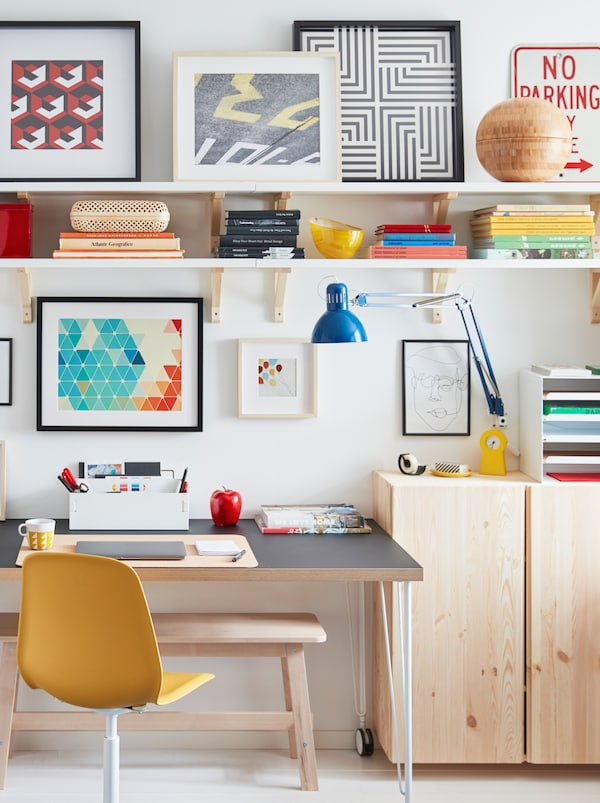 Un birou pe rotile așezat lângă un perete este înconjurat de corpuri IVAR din lemn ușor, polițe de perete și lucrări de artă înrămate.
