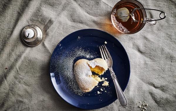 Un biscuit en forme de cœur fourré à la crème vanille et une fourchette sur une assiette bleu foncé, une tasse de thé et une bougie.