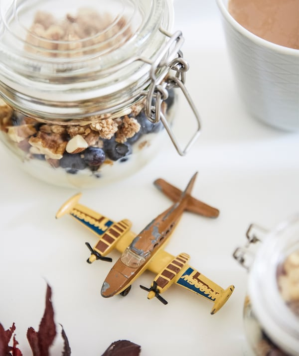 Un bocal en verre rempli de granola et un petit avion sur une surface blanche.