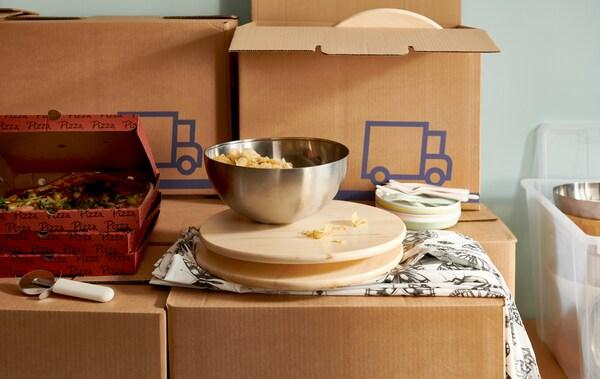 Un bol BLANDA BLANK contenant des croustilles sur un plateau tournant et des boîtes de pizza sont disposés sur des piles de boîtes de déménagement JÄTTENE.