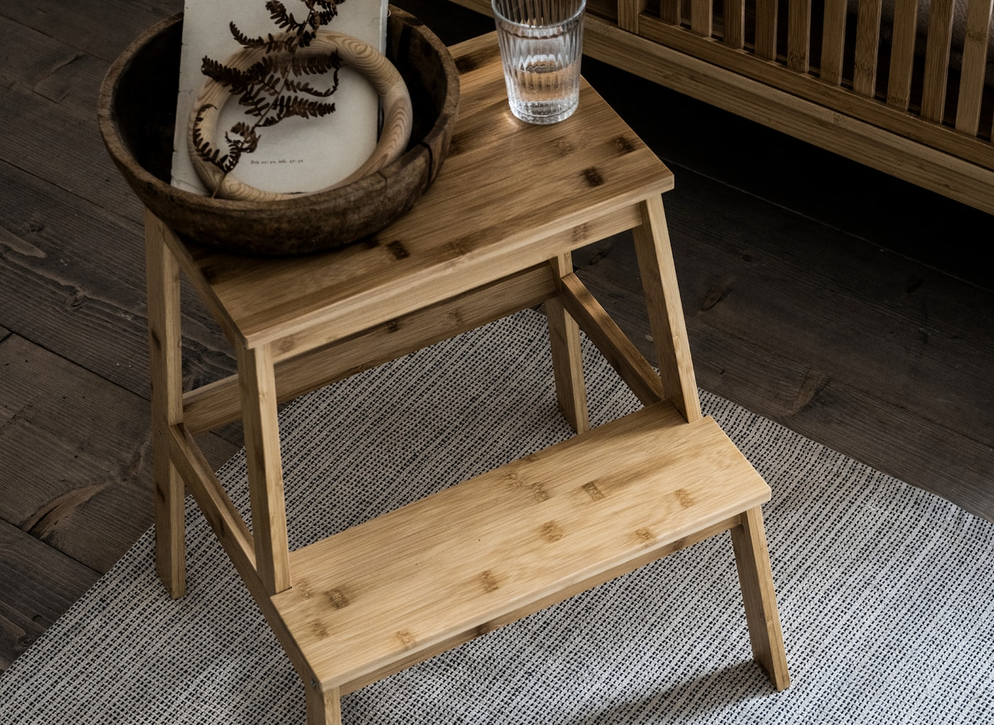 Un bol en bois et un verre transparent sont posés sur un marchepied TENHULT de IKEA en bambou.
