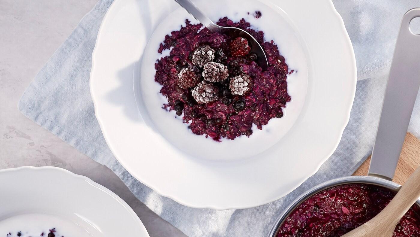 Un bol en porcelaine blanche contenant du gruau HJÄLTEROLL, des petits fruits et une cuillère sur une serviette de table blanche, près d'une casserole en métal.