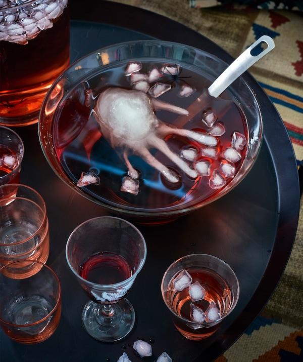 Un bol rempli de punch rouge et de glaçons, dont un en forme de main, et des verres déposés sur une table noire.