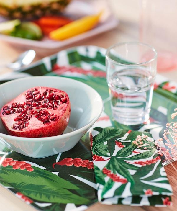 Un bout de table avec une moitié de grenade dans un bol blanc placé sur un plateau rouge et vert SOMMARLIV avec la serviette en papier assortie.