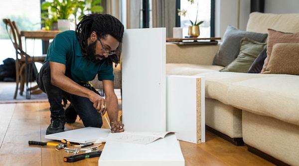 Un bricoleur TaskRabbit assemble un meuble IKEA dans la maison d'un client.
