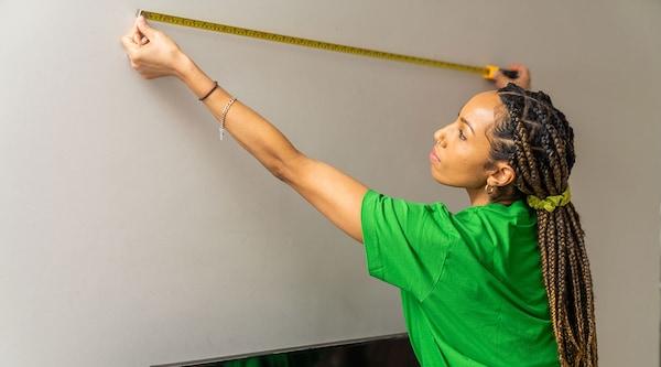 Un bricoleur TaskRabbit installe un support mural pour téléviseur.
