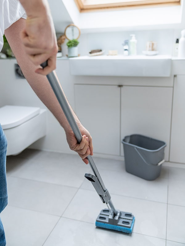 Un bricoleur TaskRabbit passe la vadrouille sur le plancher d'une salle de bains.