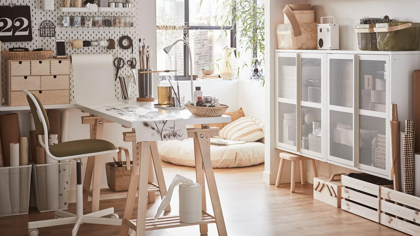 Un bureau à domicile lumineux avec un bureau blanc, une chaise pivotante blanche et jaune et un panneau perforé blanc où sont suspendus des matériaux de bricolage.
