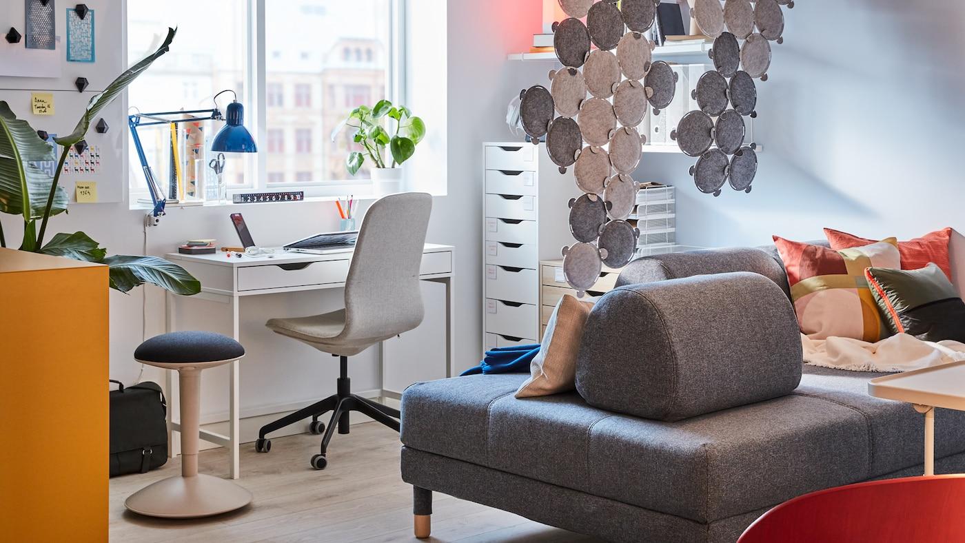 Un bureau à la maison dans le salon avec un bureau blanc et des caissons à tiroirs, une chaise de bureau grise, un canapé gris et des panneaux acoustiques.