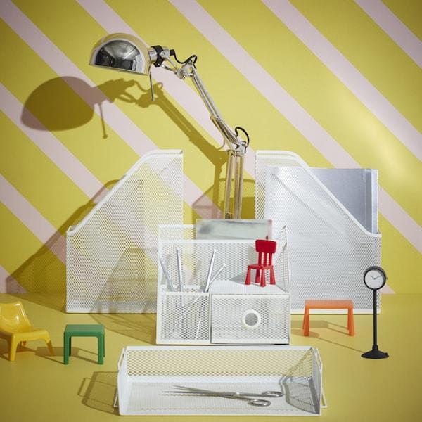 Un bureau avec une lampe de table et divers accessoires d'organisation de bureau en filet blanc.