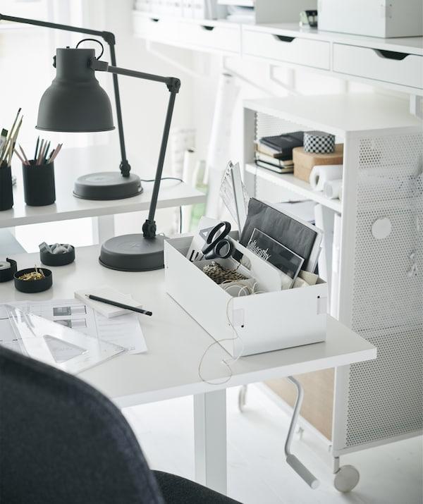 Un bureau blanc avec un organiseur et une lampe de bureau gris foncé.
