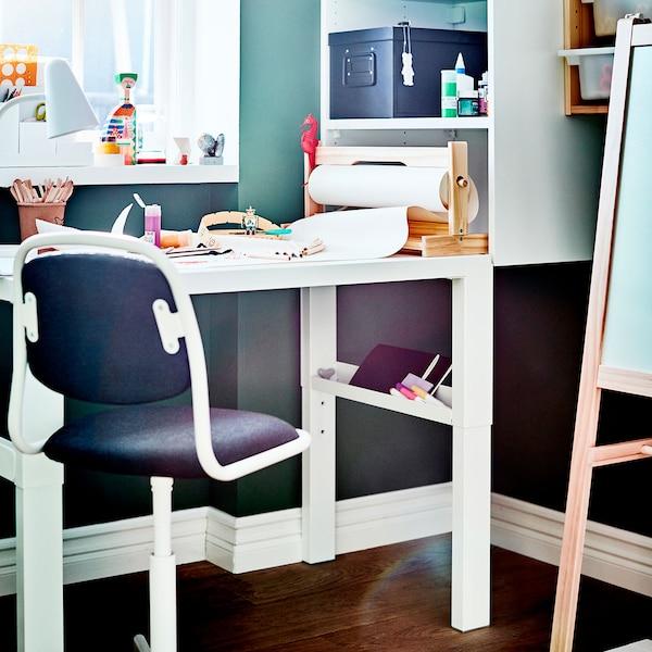 Un bureau blanc pour enfant et une chaise bleu foncé, avec des fournitures artistiques sur le bureau.
