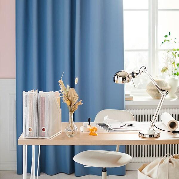Un bureau en bois pâle, placé en avant d'une fenêtre avec un rideau bleu ciel.