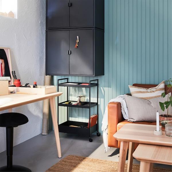 Un bureau en bouleau plaqué, un tapis en jute, deux armoires murales et une desserte noires, et un canapé en cuir brun-rouge.