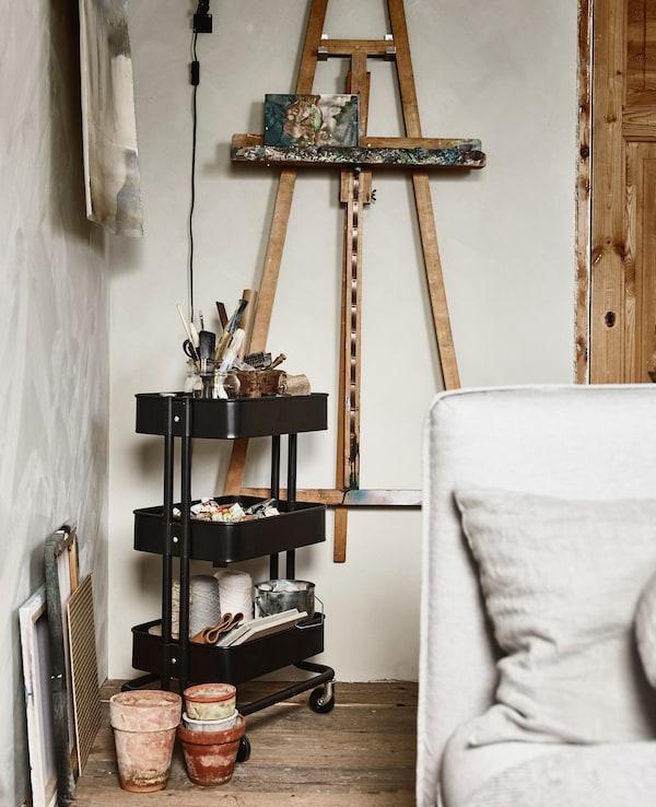 Un caballete colgado en una pared, y un carrito con material artístico al lado.