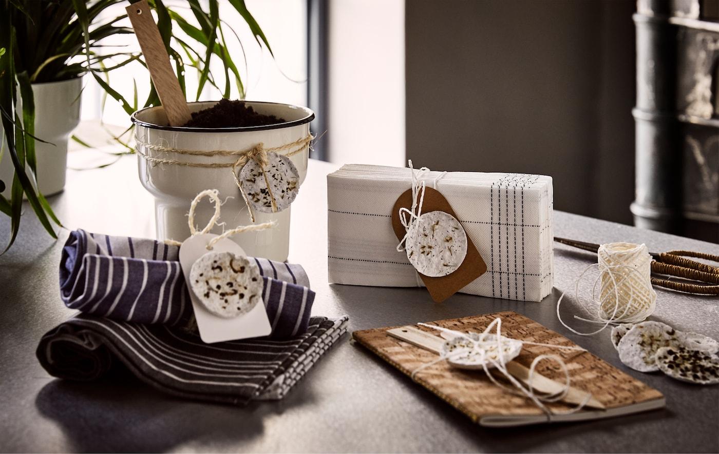 Un cache-pot beige, un carnet brun, des serviettes en tissu et en papier avec des dosettes de plantes faites maison nouées autour.