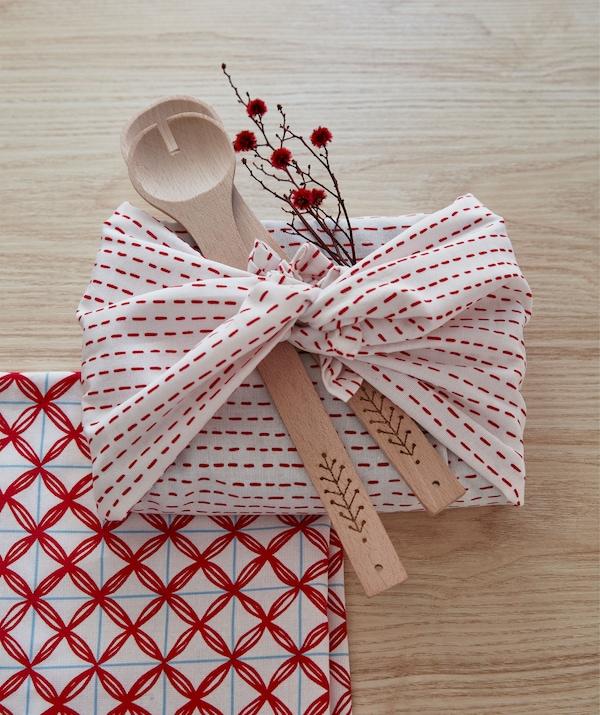 Un cadeau rectangulaire emballé dans un morceau de tissu noué, décoré d'ustensiles en bois et d'un rameau fleuri.
