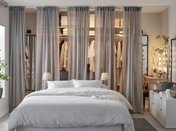 Un cadre de lit blanc, une penderie à moitié cachée par des rideaux gris, une commode blanche et un tapis gris.