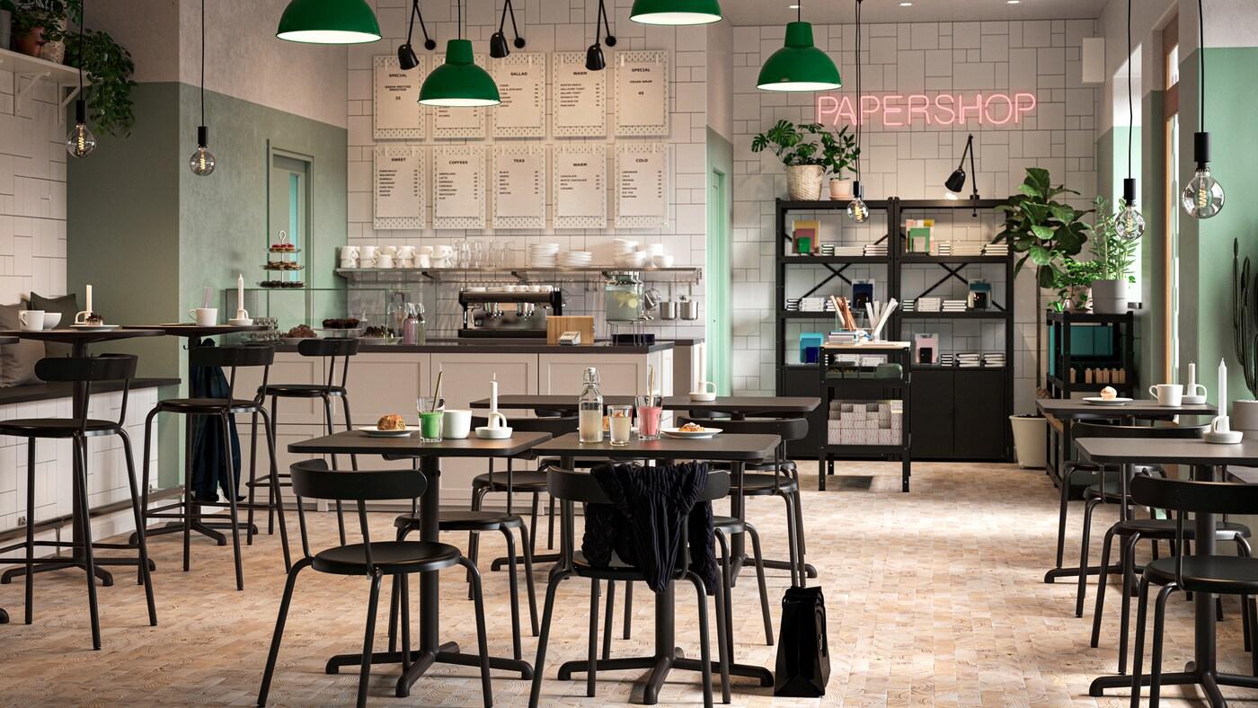 Un café avec des tables et des chaises noires, des murs blancs et verts, un kiosque papeterie, des lampes suspendues vertes et des plantes.
