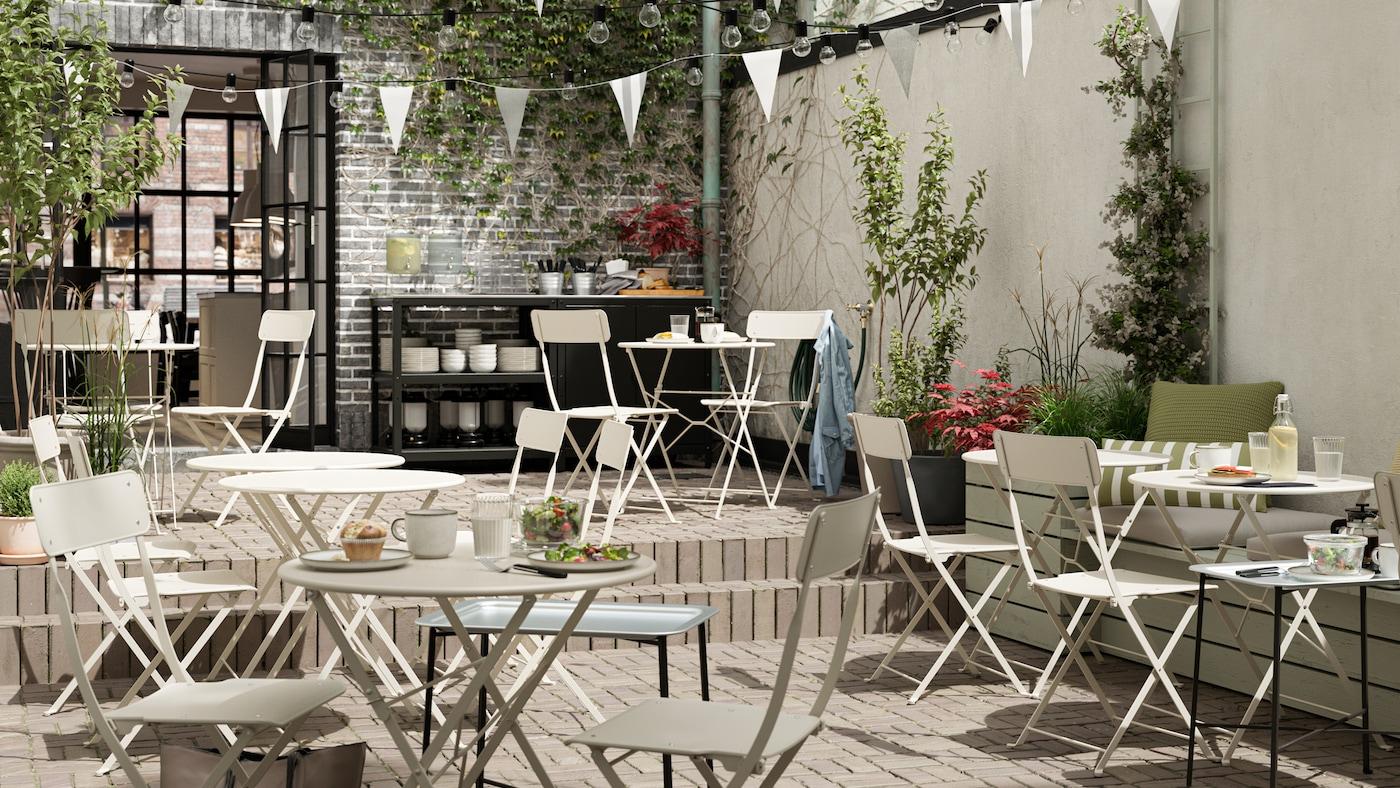 Un café extérieur avec des tables et des chaises pliables en acier beige, des fanions blancs, un plancher carrelé et un comptoir de service.