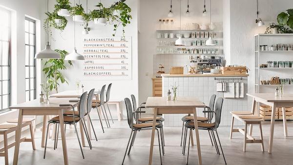Un café moderne beige, noir et blanc avec des tables en bouleau blanc NORRÅKER et des chaises noires et chromées.