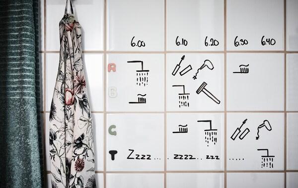 Un calendario escrito á man feito con rotulador negro, debuxado en azulexos de baño brancos.