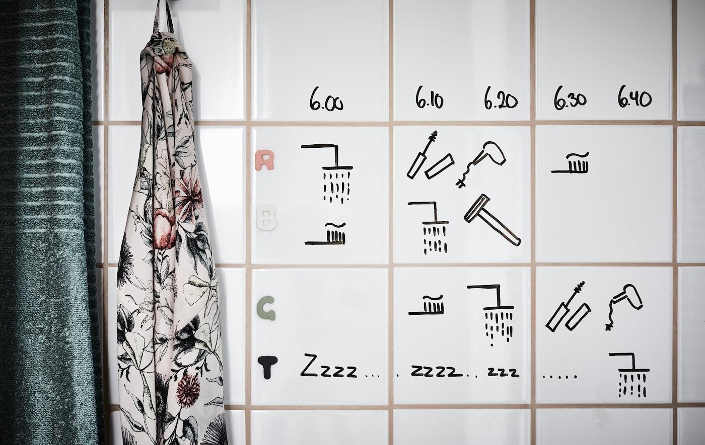 Un calendario escrito a mano hecho con rotulador negro, dibujado en azulejos de baño blancos.