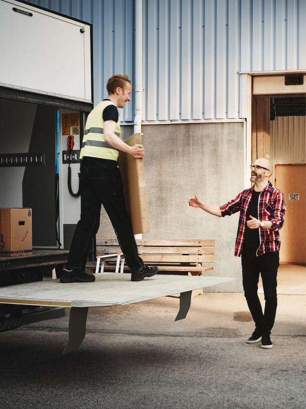 Un camion est rempli par deux hommes de paquets plats IKEA sur le quai de chargement d'une usine.