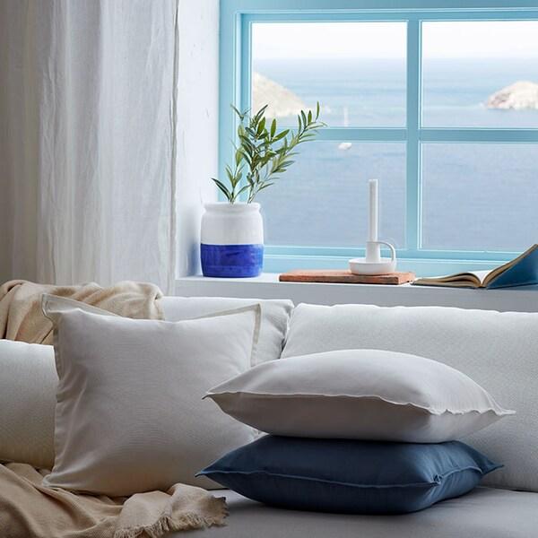 Un canapé blanc où sont empilés des coussins dans des housses bleues et blanches, devant une fenêtre avec un vase de verdure, face à la mer.