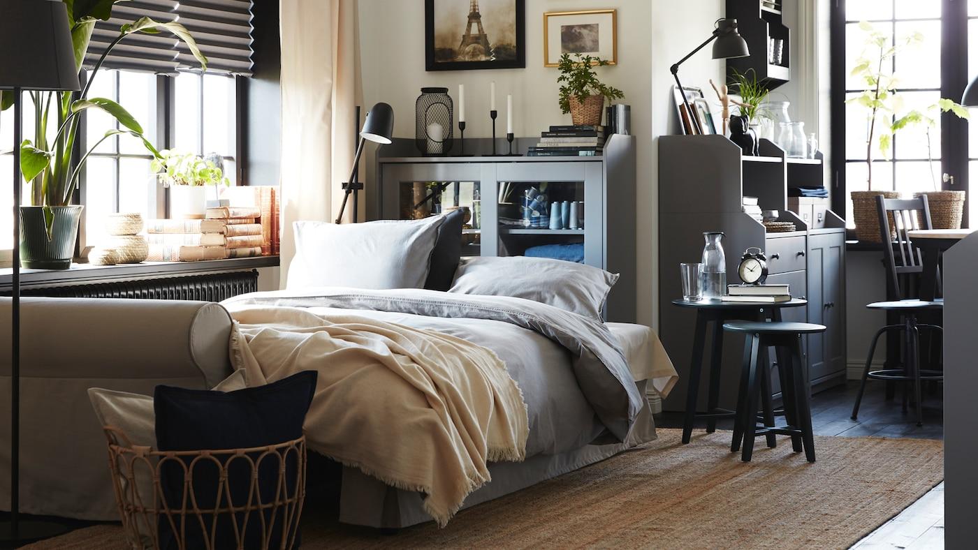 Un canapé convertible beige clair conçu comme un lit, avec une literie grise. Derrière se trouve un élément de rangement gris avec portes vitrées et un tapis en jute au sol.