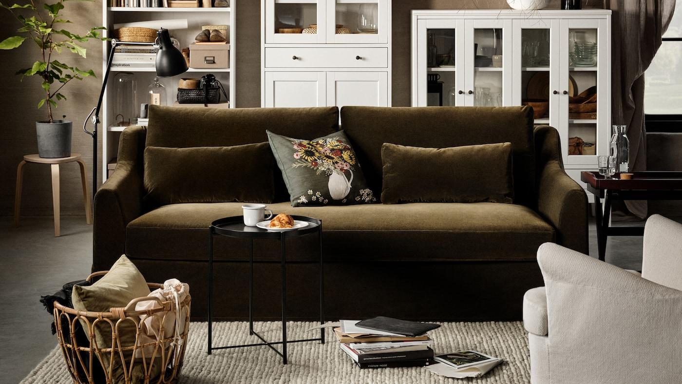 Un canapé deux places vert olive foncé, un élément de rangement haut blanc avec des portes vitrées et un tiroir, une bibliothèque blanche et un tabouret en bouleau.